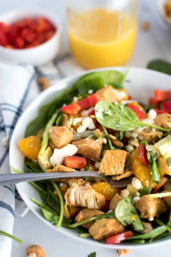 bowl of spinach salad with chicken, bell peppers, mandarin oraanges, and cheese