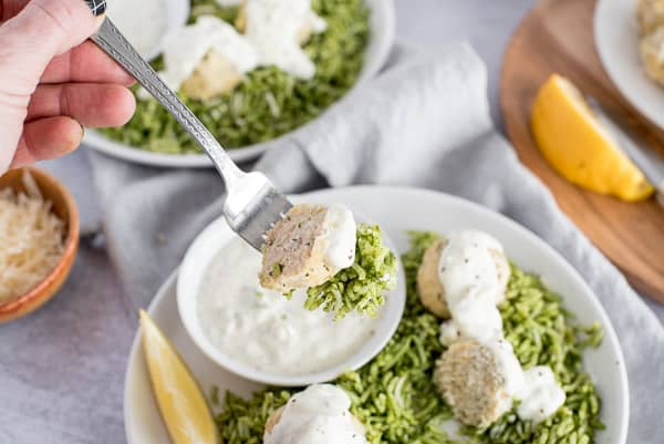 A fork of meatballs, green rice, and lemon sauce