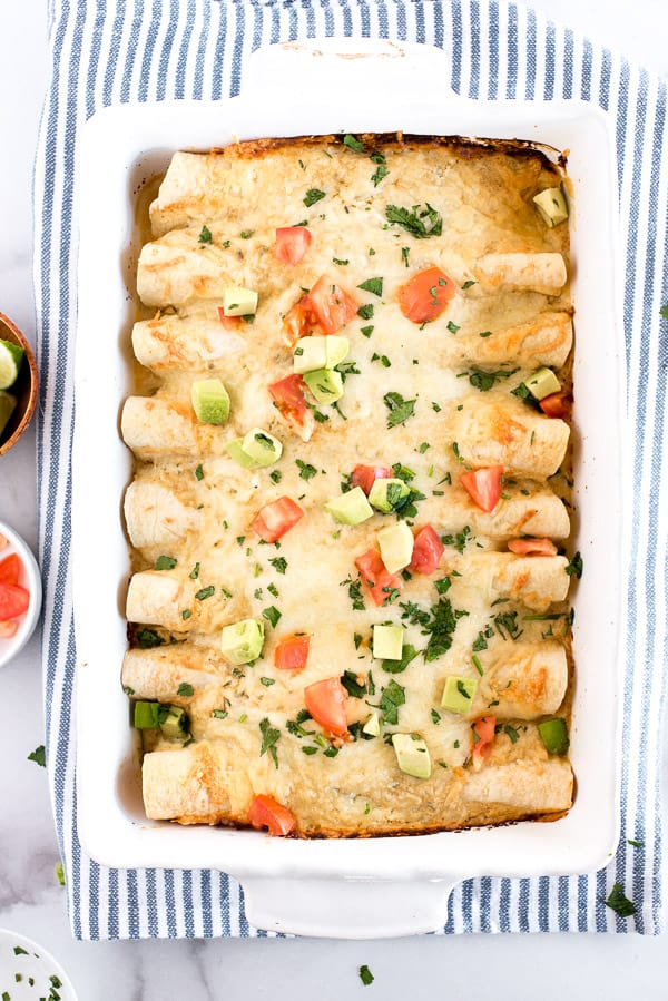 White casserole dish of chicken enchiladas with tomatoes, avocados, and sour cream