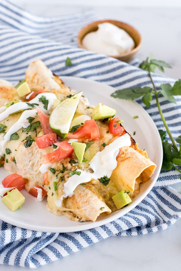 2 chicken enchiladas on a white plate with avocados and tomatoes