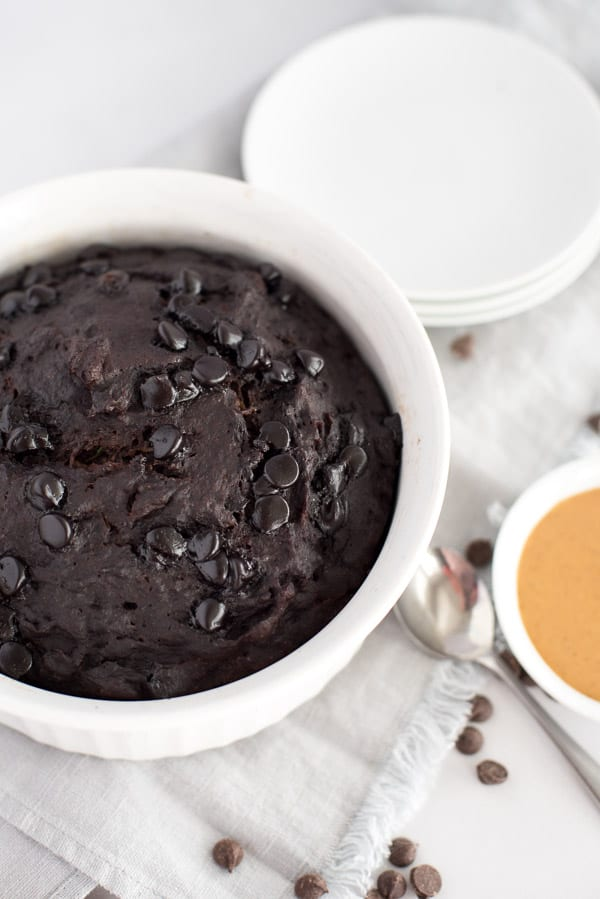 chocolate zucchini cake in a white dish with chocolate chips on top