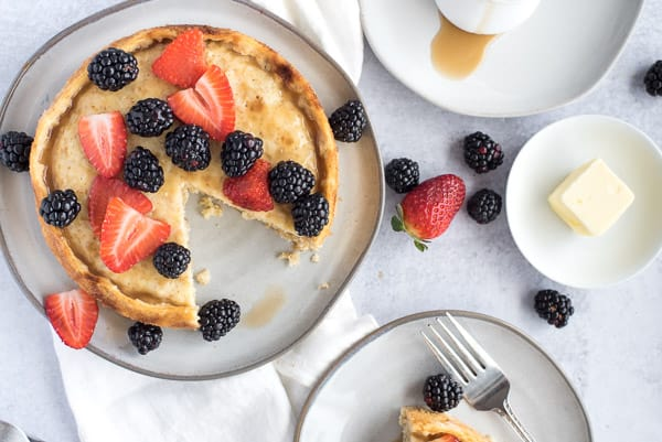 Giant pancake with a slice on a white plate with berries