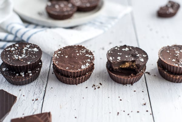 Chocolate peanut butter cups stacked on top of each other on a white surface