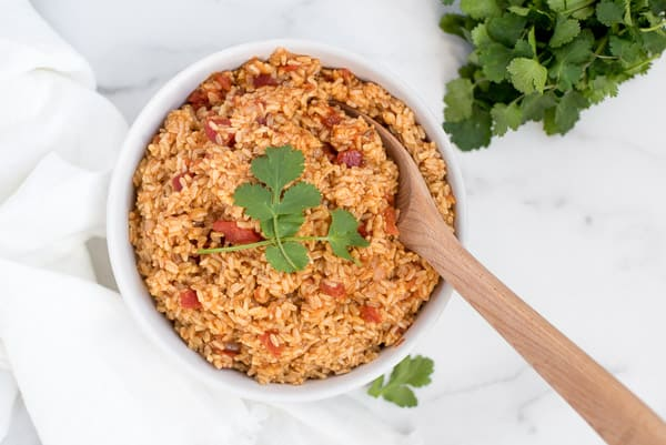 mexican rice with tomatoes in a white dish with a wood spoon