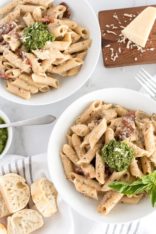 2 bowls of pasta with sun-dried tomatoes and pesto