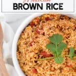 mexican rice with tomatoes in a white dish with cilantro