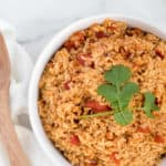 mexican rice with tomatoes in a white dish