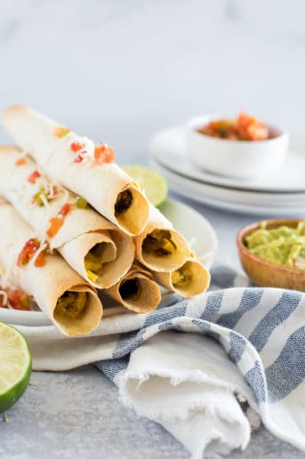 pile of breakfast taquitos with salsa and guacamole