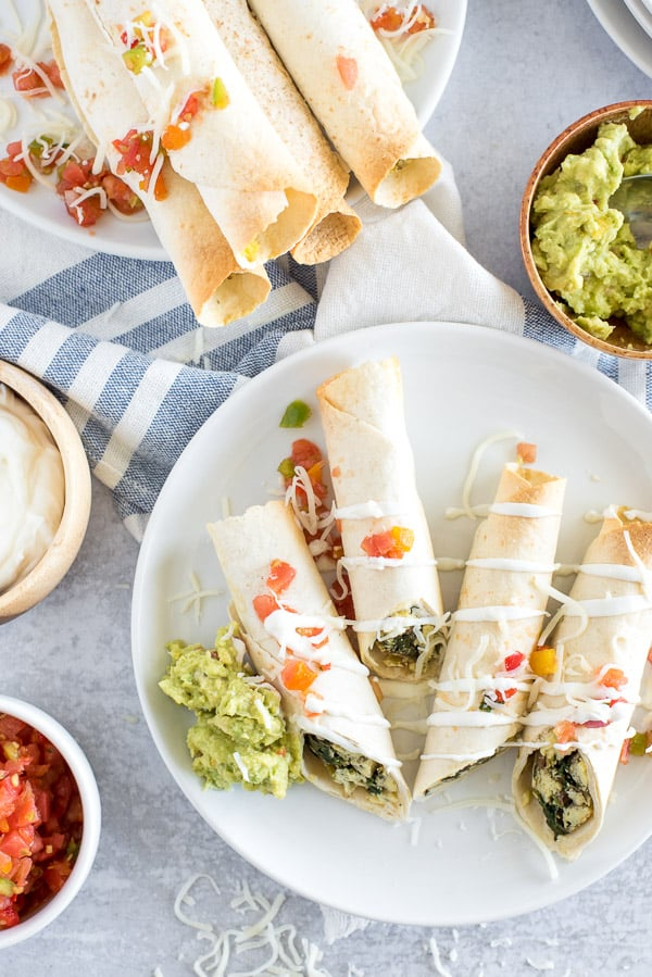 taquitos cut in half on a plate with sour cream and guacamole