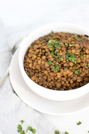 Instant Pot Lentils in a white bowl garnished with parsley
