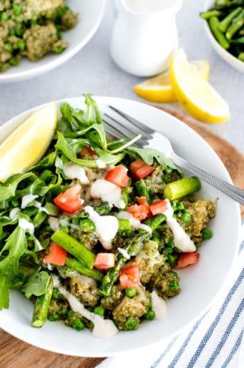 white bowl of chicken, quinoa, and vegetables with lemon slice