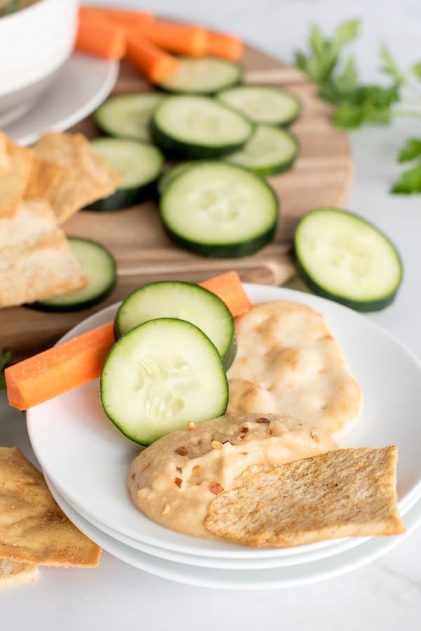 plate of hummus with a side of cucumbers, carrots, and crackers