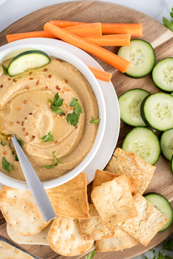 white bowl of hummus with crackers, vegetables, and herbs