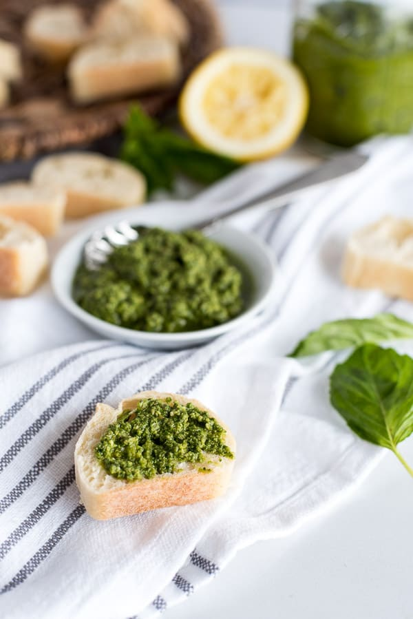 bowl of pesto and a slice of bread with pesto on top
