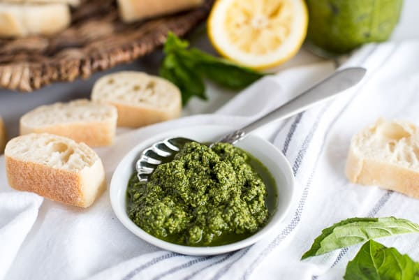 White bowl of pesto with a spoon and bread slices in the background