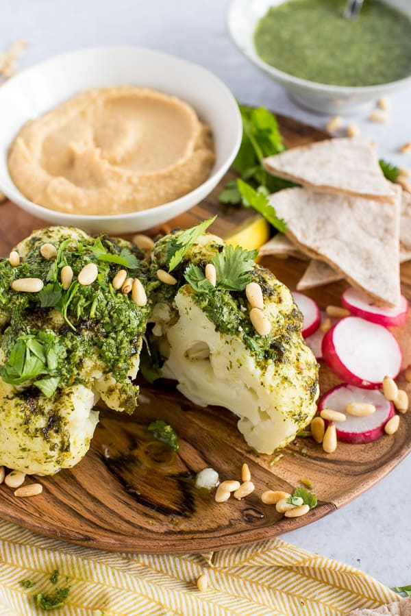 head of cauliflower with a wedge cut out, drizzled with chimichurri sauce