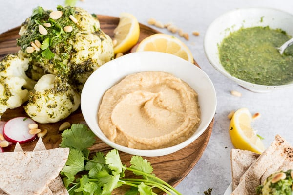 bowl of hummus next to a whole roasted cauliflower and lemon slices