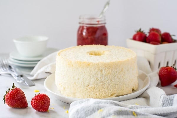 Angel food cake on a white plate next to strawberry sauce