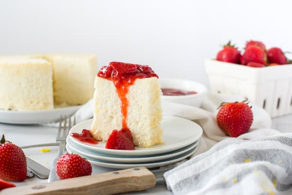 two slices of angel food cake on a white plate with strawberries and whipped cream