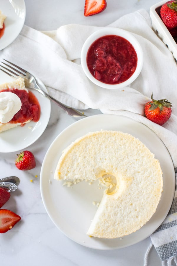 Angel food cake cut into slices and topped with strawberry sauce