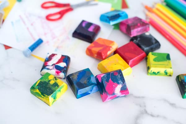 Square crayons of many different colors with scissors and paper