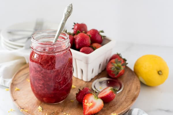 strawberry jam in a mason jar next to sliced strawberries on a cutting board