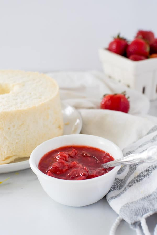 bowl of strawberry sauce next to angel food cake