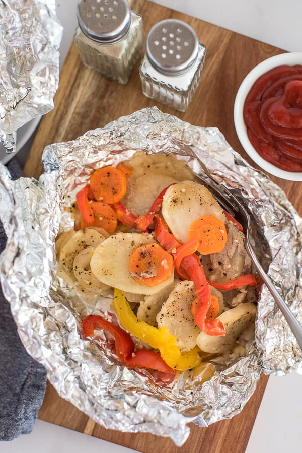 potatoes, peppers, carrots, and onions in a tinfoil packet with sauce on the side