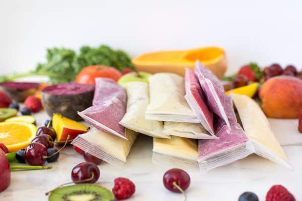 green, pink, yellow, and purple yogurt tubes in a row surrounded by fruits and vegetables