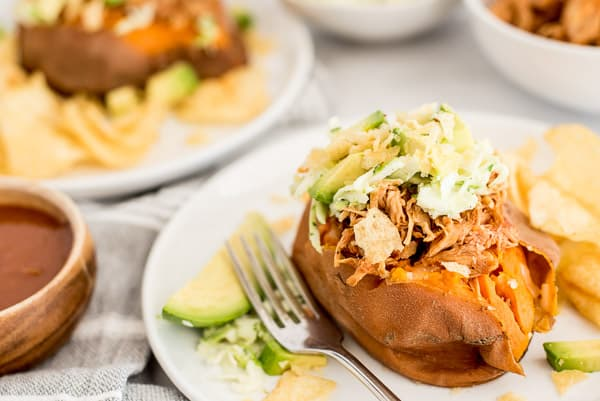BBQ chicken stuffed sweet potato with avocados and cheese on a white plate