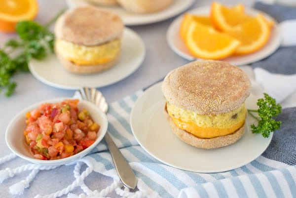 Two breakfast sandwiches with eggs, cheese, and sausage on a white plate