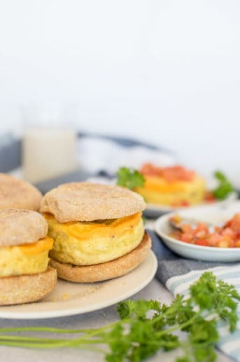 three breakfast sandwiches with eggs, cheese, and sausage on a white plate