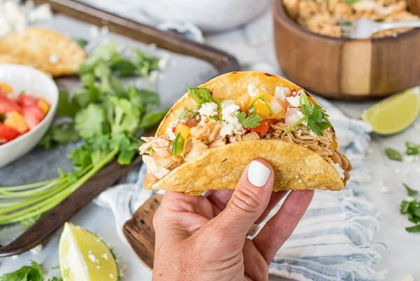 hand holding a chicken taco with peach salsa
