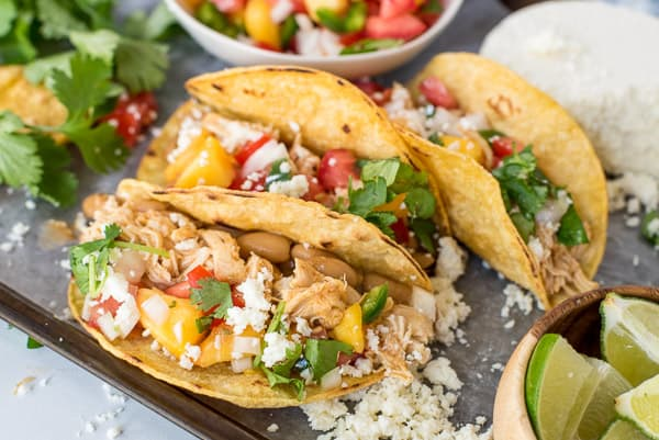 three tacos with chicken and peach salsa next to a bowl of beans and cilantro