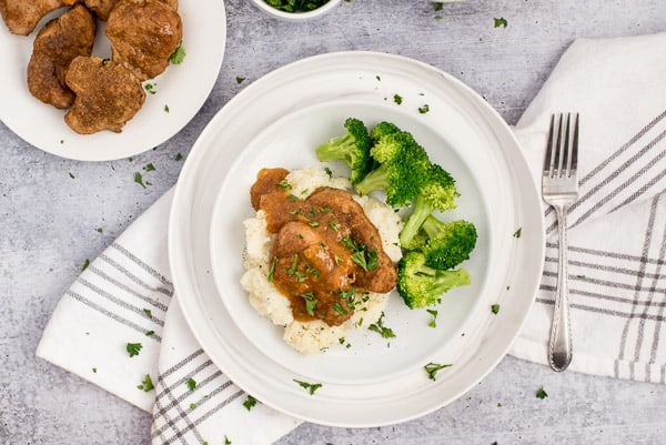 Pork chops and apricot sauce on a bed of mashed potatoes with broccoli