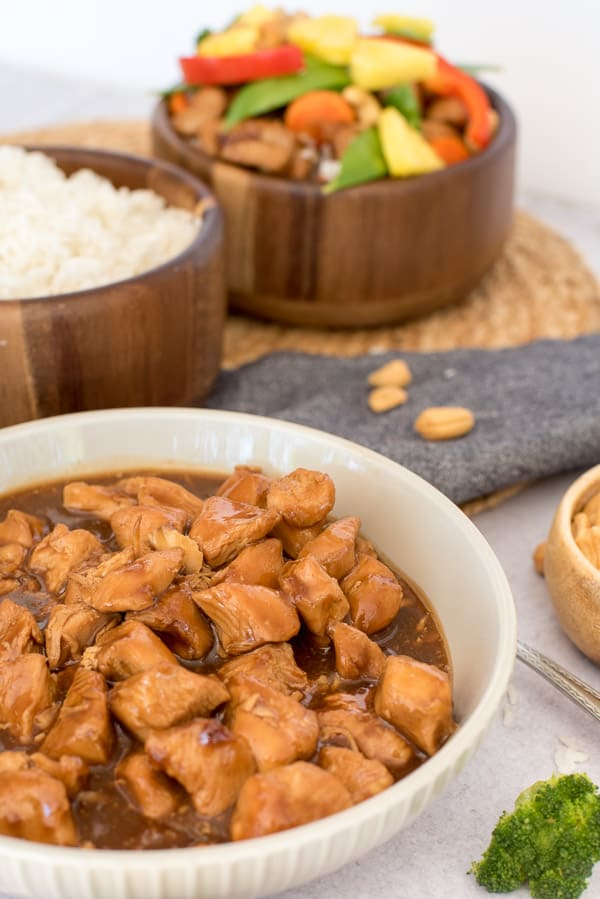white bowl with teriyaki chicken and a wood bowl with rice