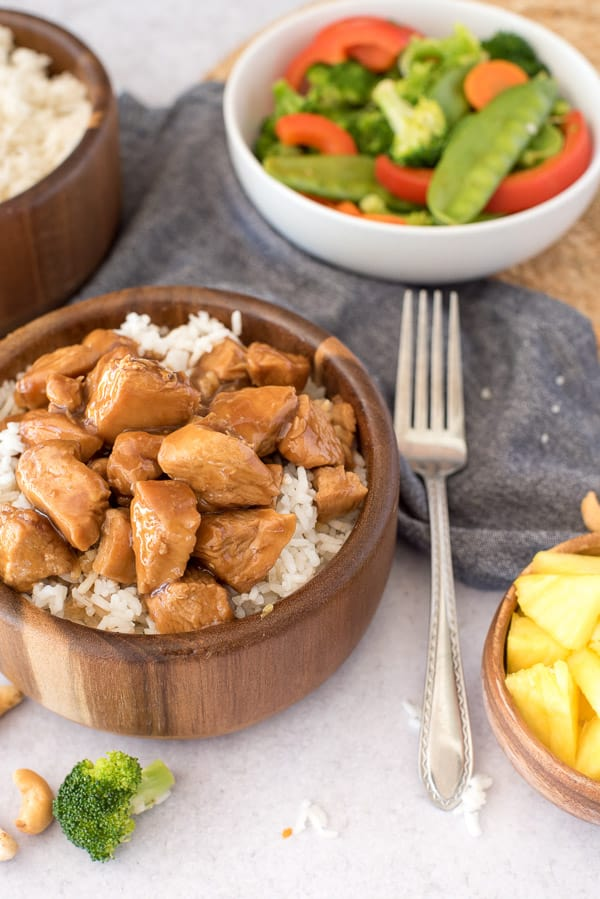 wood bowl with teriyaki chicken and rice with a white bowl of vegetables