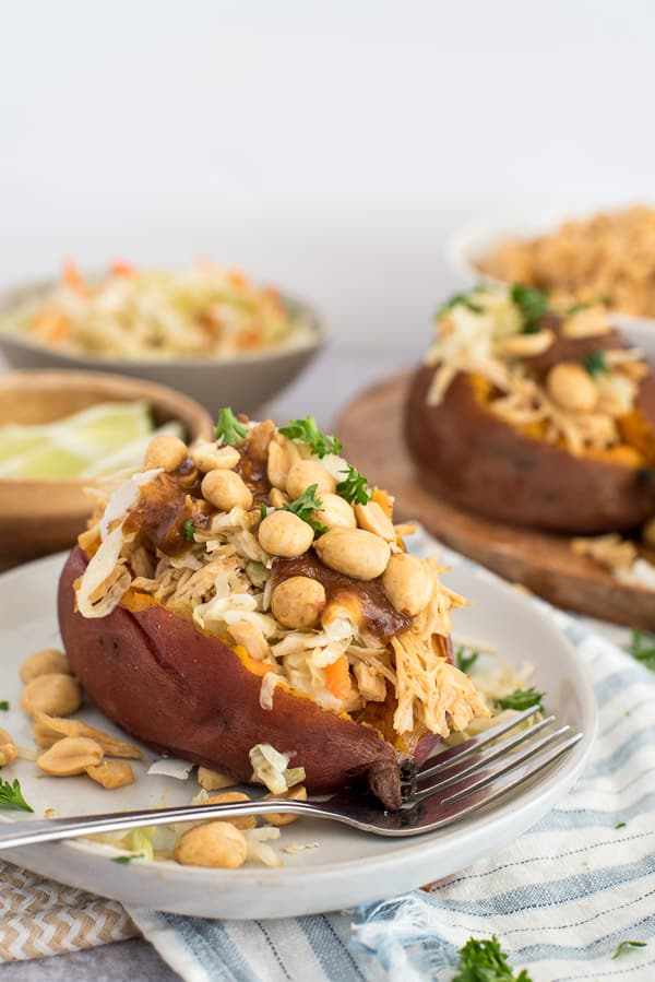 sweet potato on a white plate filled with coleslaw, peanuts, and peanut sauce