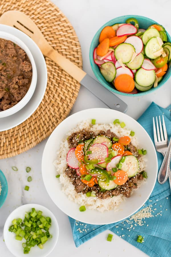 Korean Beef topped with radishes, carrots, and cucumbers in a white bowl of rice