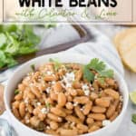 White bowl with beans, cilantro and lime with a sprinkle of cotija cheese