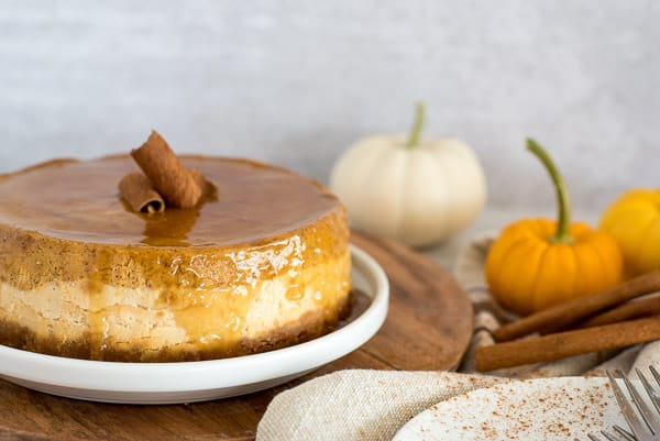 Whole pumpkin cheesecake sitting on a white plate with pumpkins on side
