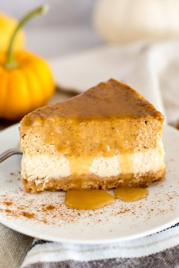 Slice of pumpkin cheesecake on a white plate with pumpkins