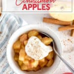 white bowl of cinnamon spiced apples topped with cream and cinnamon
