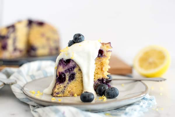 blueberry breakfast cake on a white plate with yogurt sauce