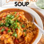 cabbage roll soup in a white bowl with a garnish of herbs