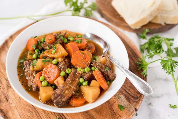 Bowl of beef stew with carrots, peas and onions in a white bowl