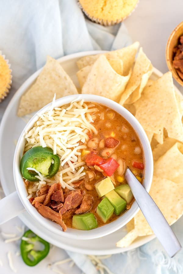 chicken chili in a white bowl with avocado, bacon, cheese, and jalapenos and a side of chips