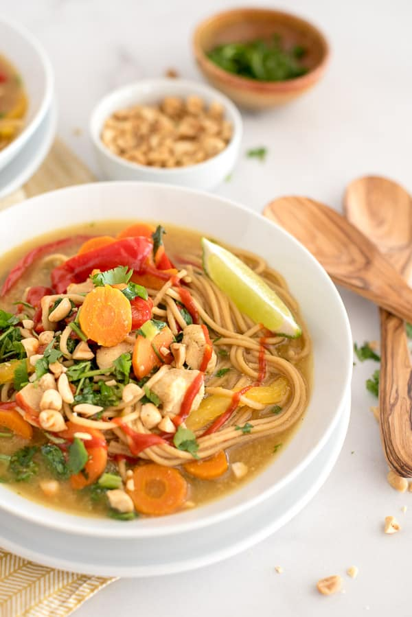 White bowl with thai soup with noodles, peppers, and cilantro