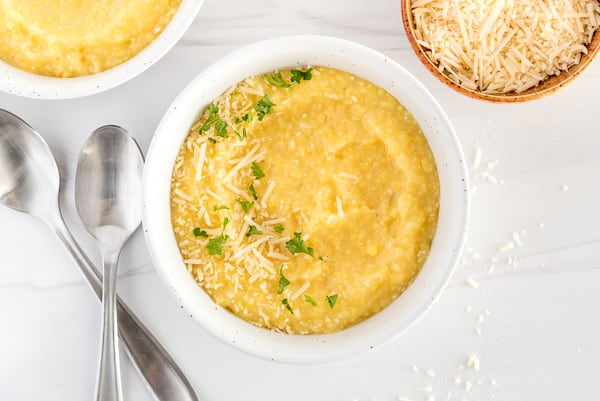 Creamy polenta in a white bowl garnished with herbs and cheese
