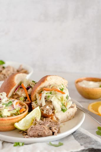 Pulled Pork Sandwiches on white plates topped with coleslaw and mayo